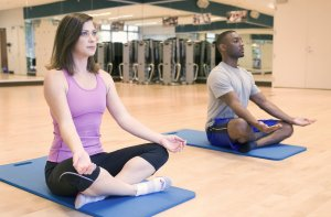 -a-man-and-woman-practicing-yoga-in-a-fitness-center